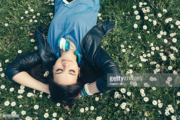 Teenage girl lying down in the grass