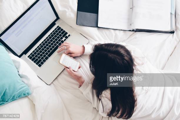 Teenage girl lying in bed using her laptop and mobile phone