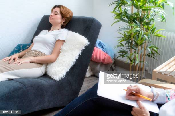 a teenage girl lying on a sofa with her psychotherapist - psychiatrist's couch stock pictures, royalty-free photos & images