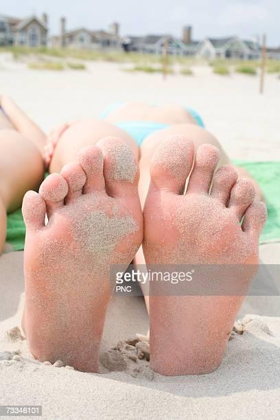 Teenage girl (15-18) lying on beach, close-up of feet