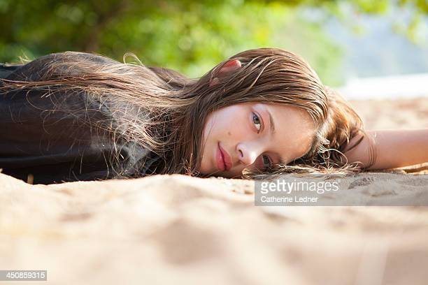 Teenage girl lying on beach