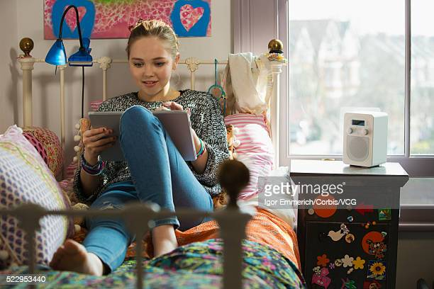 Teenage girl lying on bed and using digital tablet