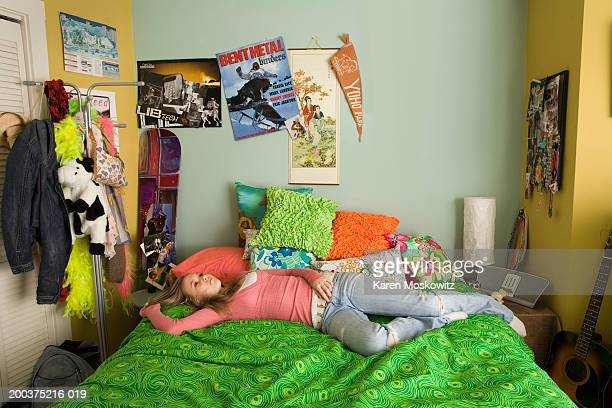 Teenage girl (14-16) lying on bed, staring at ceiling, elevated view