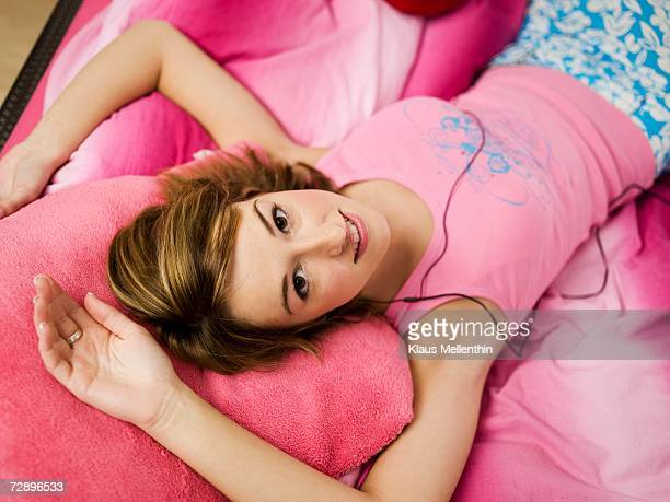Teenage girl lying on bed, using mp3 player, portrait