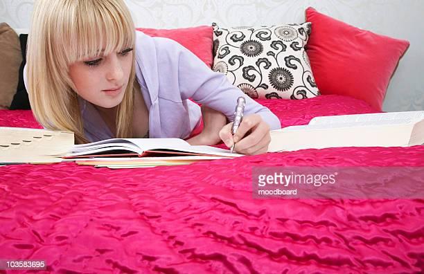 Teenage girl (16-17) lying on bed, writing