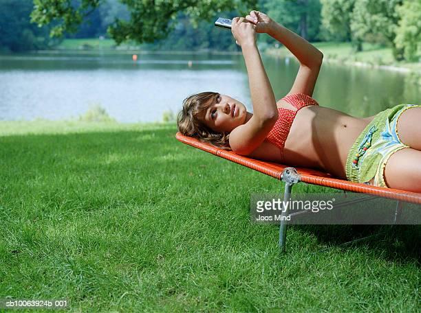 Teenage girl (14-15) lying on deckchair by lake, looking at mobile phone