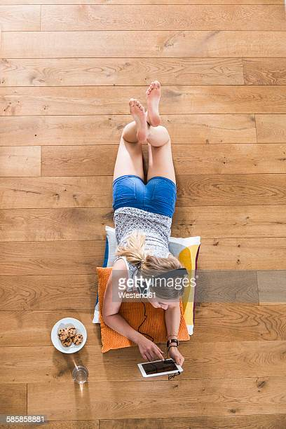 Teenage girl lying on floor listening to music from digital tablet