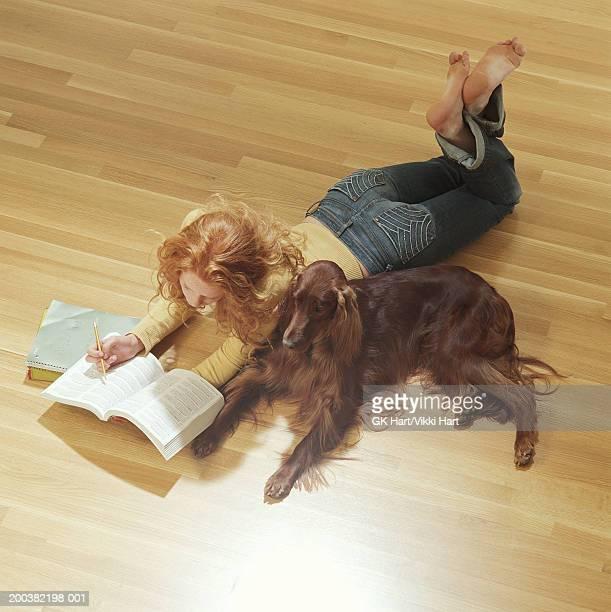 teenage girl (15-17) lying on floor with dog reading - 近く ストックフォトと画像