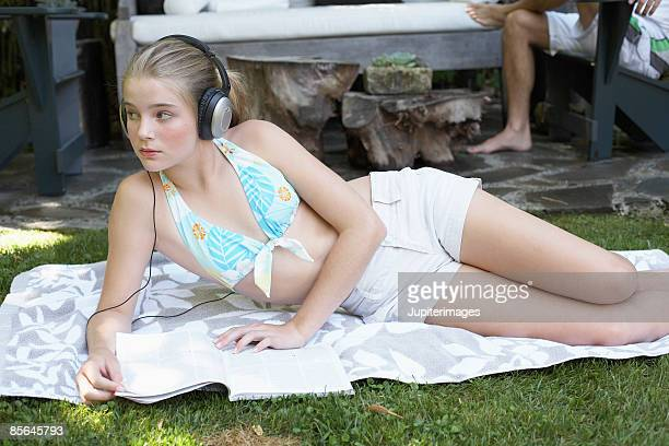 Teenage girl lying on ground reading book and listening to music