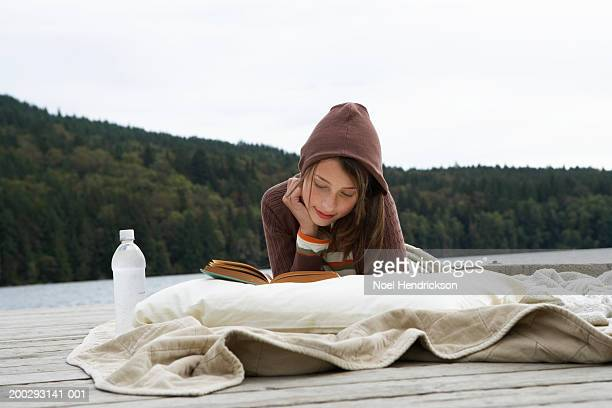 Teenage girl (13-15 years), lying on jetty by lake, leaning on pillow, reading book