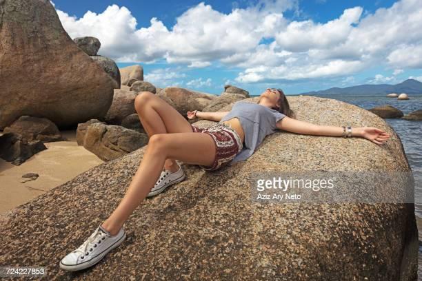 Teenage girl lying on rock sunbathing