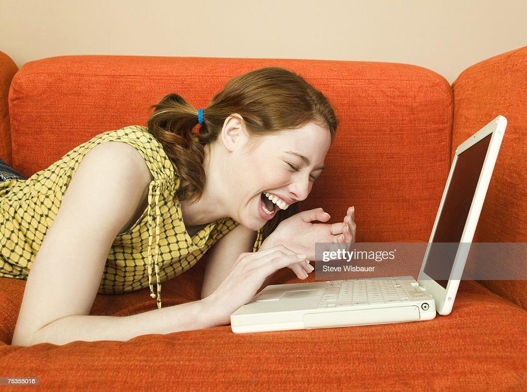 Teenage girl (16-18) lying on sofa using laptop, laughing : Bildbanksbilder
