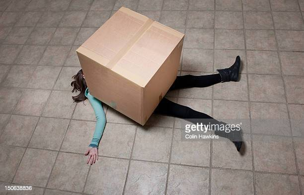 teenage girl lying under cardboard box - colin hawkins stock pictures, royalty-free photos & images