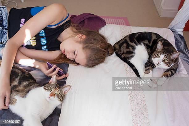Teenage girl lying with cats, using smartphone