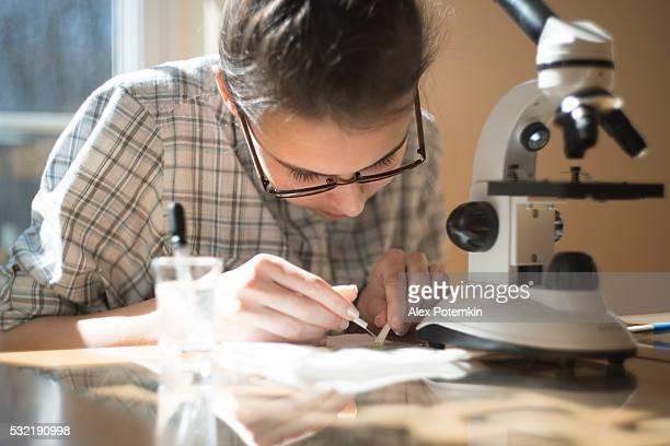 Teenager-Mädchen machen Hausaufgaben wissenschaftlichen Projekt mit Mikroskop