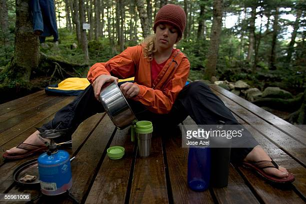 a teenage girl makes herself tea on a tent platform in a wilderness campsite. - appalachian trail stock photos and pictures