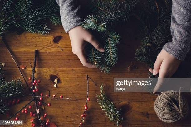 teenage girl making a christmas wreath - spruce tree stock pictures, royalty-free photos & images