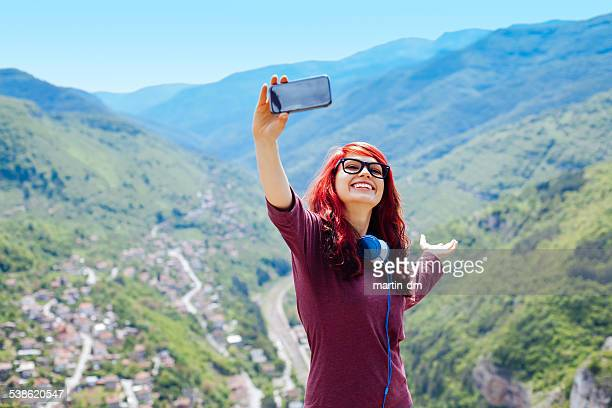 Teenage girl making a selfie in the mountain