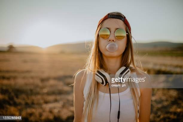 adolescente haciendo globo de goma de mascar en un día soleado de verano - música pop fotografías e imágenes de stock
