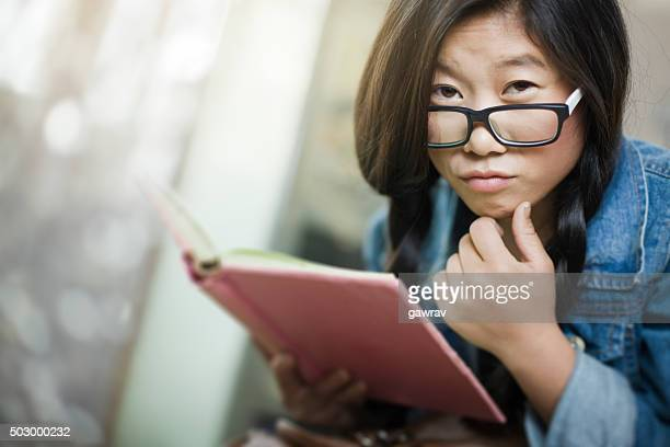 Teenager-Mädchen machen Gesicht, Blick in die Kamera und halten buchen.