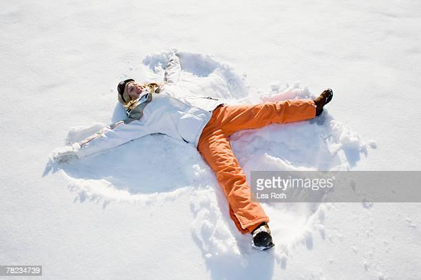teenage girl making snow angel