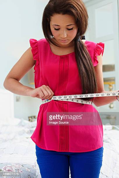 teenage girl measuring her waist - eating disorder stock pictures, royalty-free photos & images