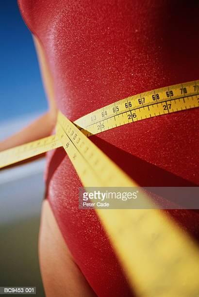 teenage girl (13-15) measuring waist with tape measure, close-up - human body part foto e immagini stock