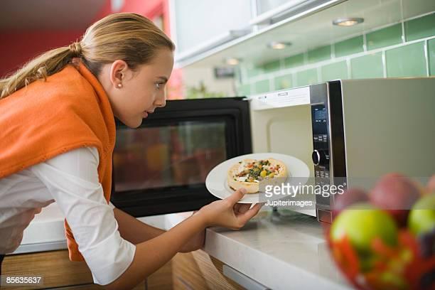 Teenage girl microwaving frozen pizza