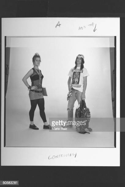 Teenage girl modeling see-through sleeveless blouse, miniskirt over black tights, clunky shoes, hoop earrings & peace symbol necklace w. Boy sporting...