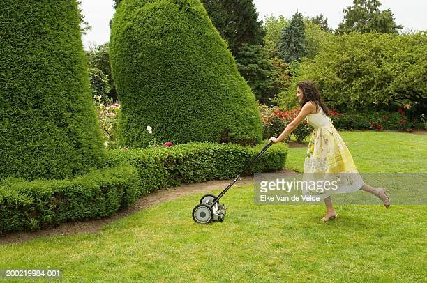 teenage girl (16-18) mowing lawn, side view - jardinier humour photos et images de collection