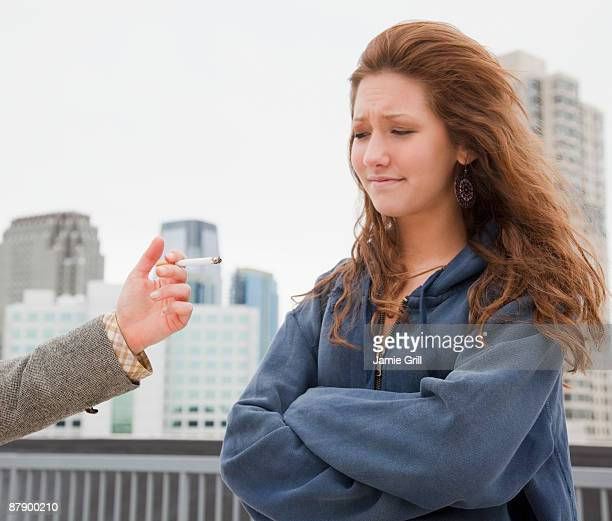 Teenage girl next to friend offering cigarette