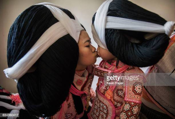 A teenage girl of the Long Horn Miao ethnic minority group kisses her younger sister as they wear headdresses in their home before Tiaohua or Flower...