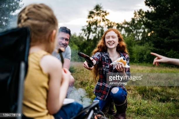 teenage girl offering young sister burnt sausage at cookout - real people stock pictures, royalty-free photos & images