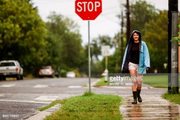 Teenage girl on a sidewalk in the rain wearing a blue raincoat in Austin Texas