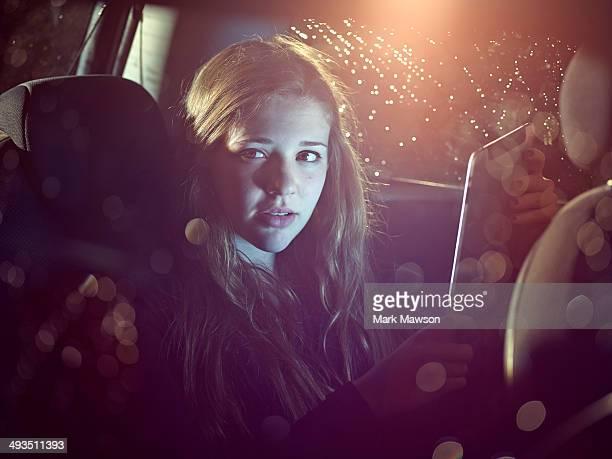 teenage girl on an iPad in a car at night