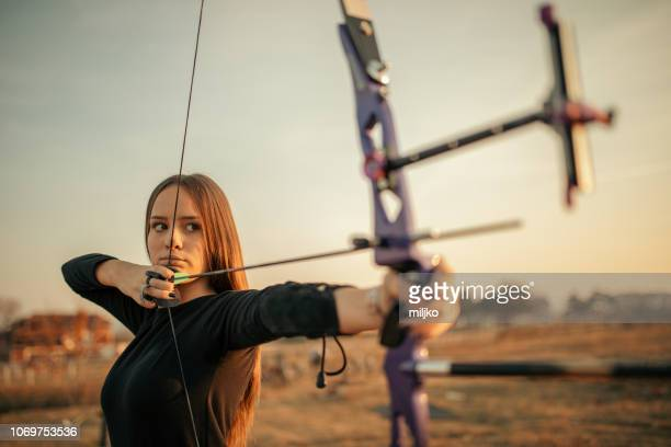 teenage girl on archery training at sunset - archery stock pictures, royalty-free photos & images