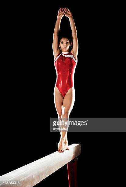 Teenage girl on balance beam.