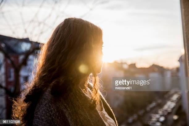 teenage girl on balcony at evening twilight - alleen één tienermeisje stockfoto's en -beelden