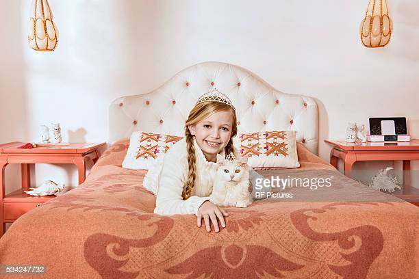 Teenage girl (13-15) on bed petting white cat