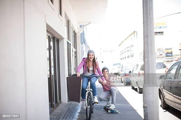 Teenage girl on bicycle pushing young man on skateboard