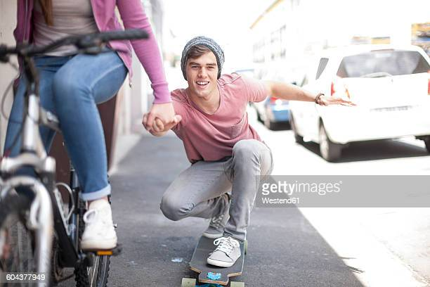 Teenage girl on bicycle pushing young man on skateboard