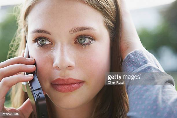 Teenage girl on cell phone crying