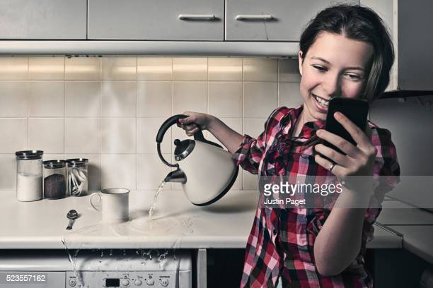 Teenage Girl on Phone whilst Pouring Kettle