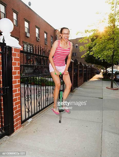 Teenage girl (14-15) on pogo stick on sidewalk