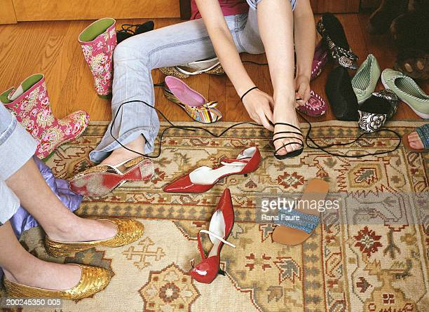 teenage girl (16-18) on rug trying on shoes, low section - floorboard stock photos and pictures