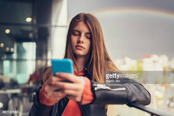 Teenage girl on terrace texting