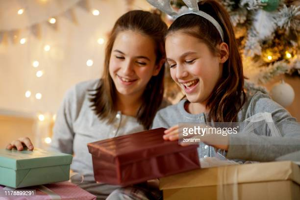 teenage girl opening gifts with friend and smiling - girl mound stock pictures, royalty-free photos & images