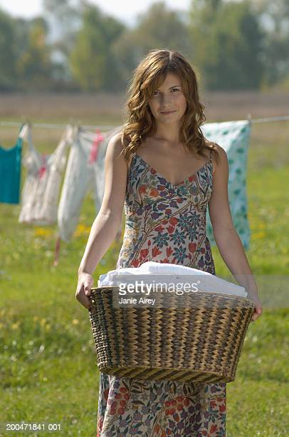 Teenage girl (16-18) outdoors, carrying laundry basket, portrait