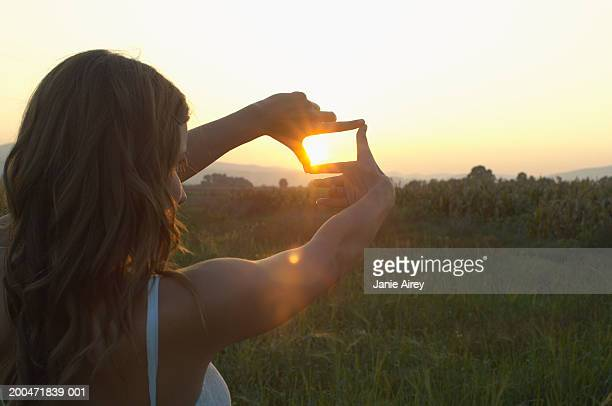 Teenage girl (16-18) outdoors, 'framing' sun with fingers