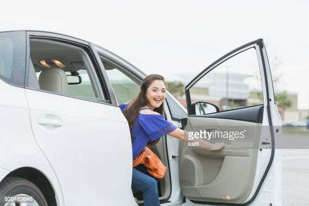 Teenage girl, passenger looking out car door